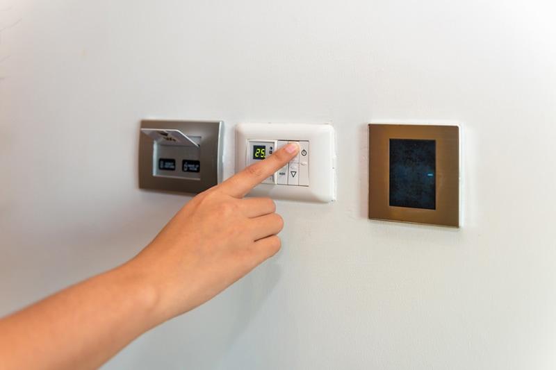 person adjusting thermostat, Heat Pump Versus Furnace