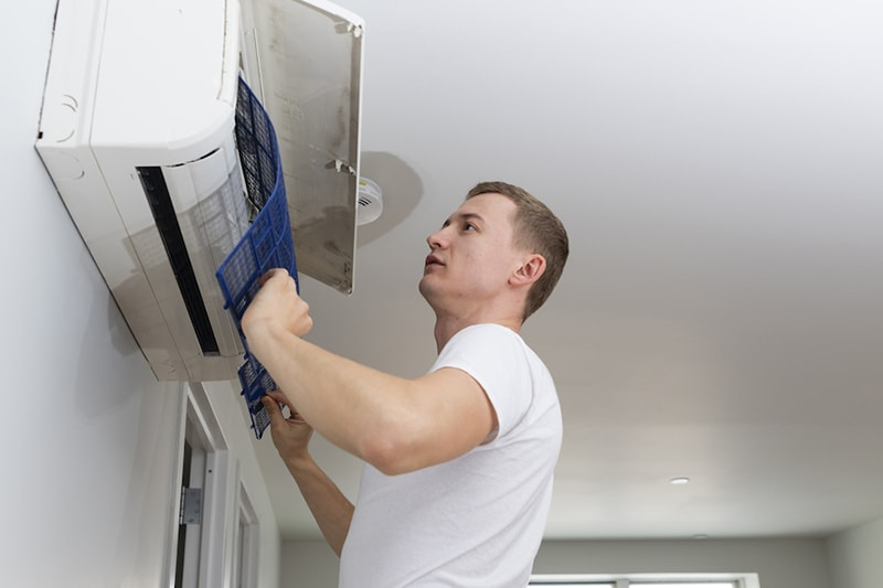 The young man cleaning filters in the air-conditioning split device in the recently rented apartment in Brooklyn, New York, USA