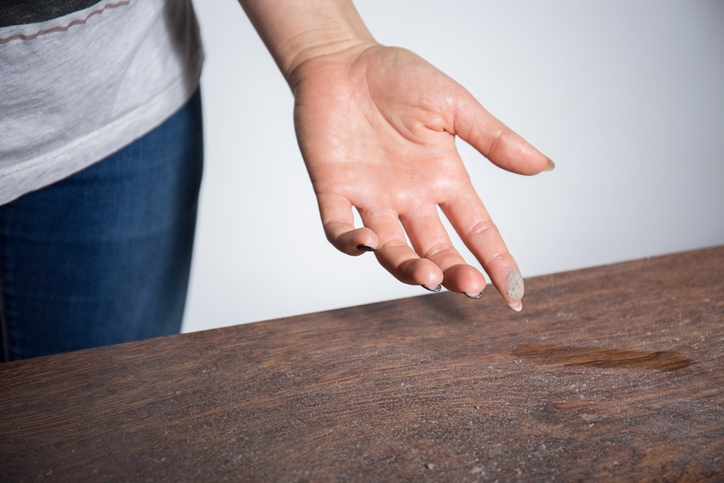 dust on a table inside a woman's home showing the possible difference between a air filter and an air cleaner