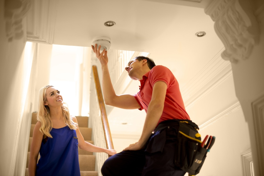 HVAC technician checking woman's carbon monoxide detector to ensure it is working and prevent any poisoning from the toxic gas inside her home.