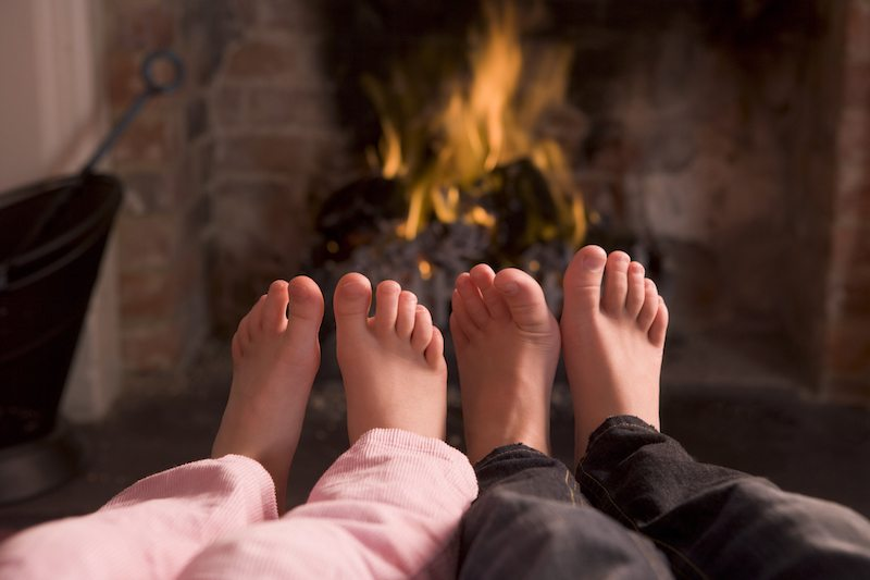 Children's feet warming at a fireplace sitting down in living room