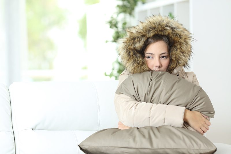 Angry woman warmly clothed in a cold home sitting on a couch; furnace blowing cold air.