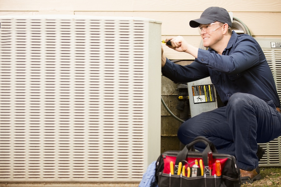 technician inspecting HVAC unit in preparation for a hurricane