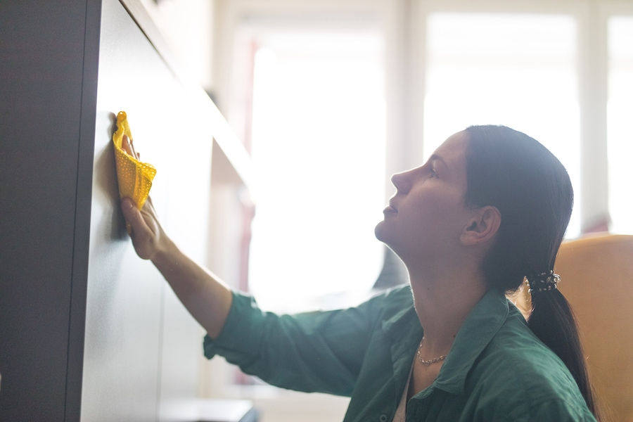 Woman cleaning furniture to help her allergies and indoor air quality.