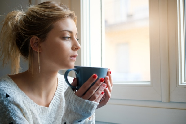why is my furnace pilot light going out?, woman with coffee mug near window